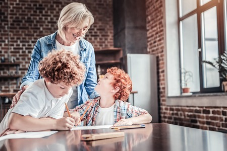 Studying at home. Delighted nice red haired boy sitting at the table and looking at his grandmother while studying at home together with her Stock Photo