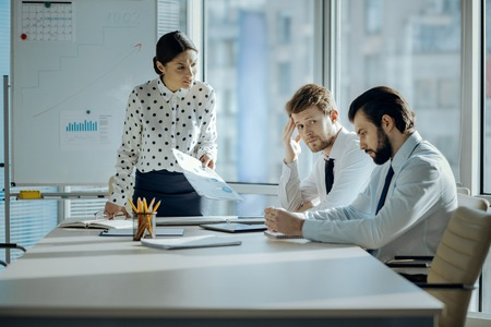 Bad job. Angry female boss having a meeting with her employees and reprimanding them for the poor performance while they looking embarrassed Stock Photo