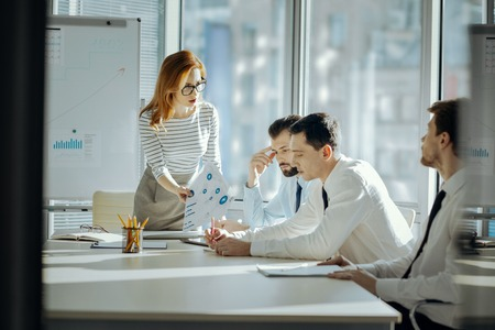 Unacceptable mistakes. Strict female boss reproaching her employees for mistakes in their work while having a meeting with them in her office and showing the printouts to them