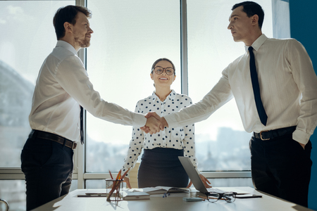 Consensus is reached. Handsome young businessmen shaking hands having negotiated a deal while their female colleague looking at them with smile Banco de Imagens - 97268953