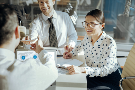 Nice result. Upbeat young colleagues sitting at the table next to their boss and submitting the printouts with copies of their research results while smiling happily
