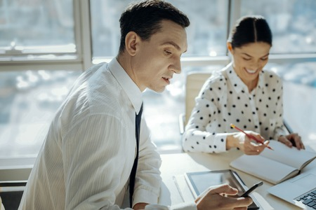 Pleasant distraction. Charming young man sitting at the table next to his female colleague and checking his phone while the woman making notes Stockfoto
