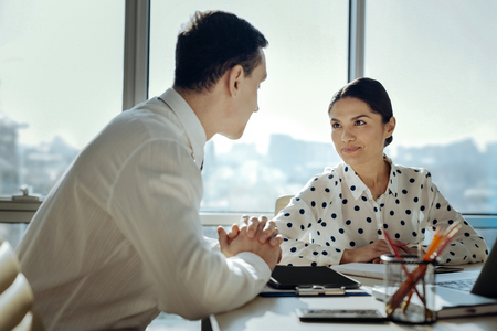 In great mood. Pretty young woman sitting at the office table with her male colleague and exchanging smiles with him while working on their common project