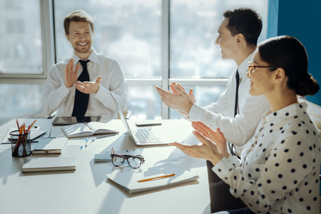 Great accomplishment. Joyful young businesspeople sitting at the table in the conference room and clapping hands, celebrating sealing the deal with a new sponsor Stockfoto