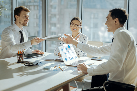 Useful printouts. Cheerful young man sitting at the table next to his colleagues and distributing copies to them before discussing project plan