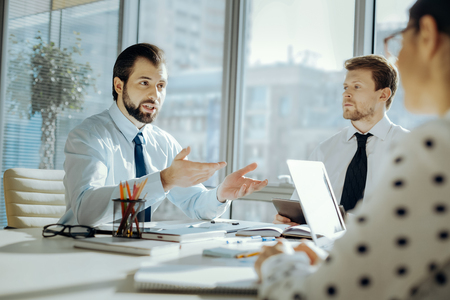 Opinionated man. Handsome young man sitting at the table and emotionally driving his point home while participating in the meeting with his colleagues Stockfoto