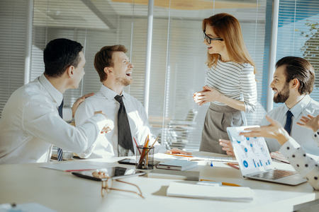 Funny jokes. Adorable young female team leader conducting a meeting with her colleagues and laughing together with them while deviating from topic of discussion
