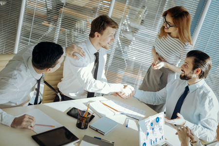 Conflict solved. Pleasant male office workers shaking hands, having reconciled with each other with the help of their colleagues and a team leader Stockfoto