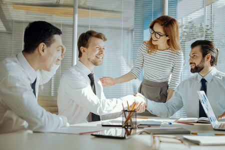 Problem solved. Caring female team leader reconciling her two male colleagues during the meeting and they laughing and shaking hands