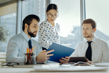 Quick and caring. Charming pleasant female secretary giving document copies to her boss while he carrying out a meeting with his business partner