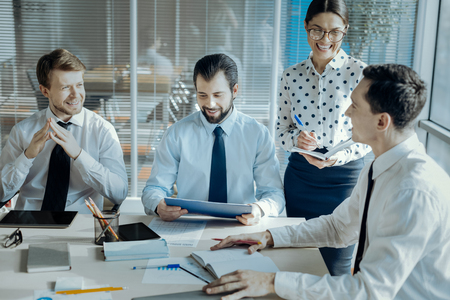 Upbeat mood. Joyful young businesspeople sitting at the table in the conference room and laughing while discussing new project, cracking jokes Stockfoto