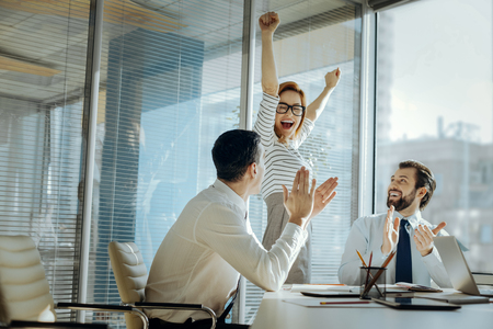 Perfect birthday. Upbeat young woman raising her hands and laughing happily celebrating her birthday while her colleagues clapping their hands and congratulating her Stockfoto