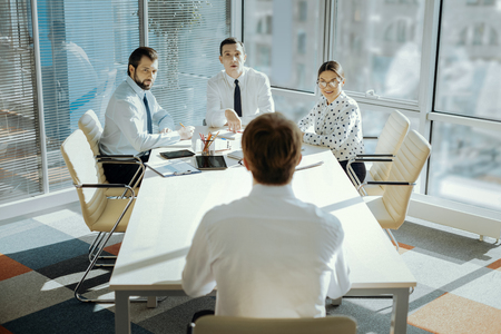 Crucial meeting. The back view of a young male CEO sitting at the head of the table and carrying out a meeting with his managers, keeping distance between himself and them