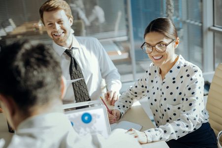 Positive ambience. Charming cheerful young woman and her male colleague sitting in their boss office and listening to his explanations while smiling at him