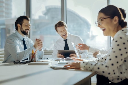 Cheerful mood. Upbeat young colleagues sitting at the table in the conference room and laughing at their boss joke during the meeting