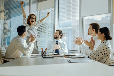 Perfect day. Adorable young woman raising her hands in joy and celebrating her promotion while her colleagues clapping their hands and congratulating her Stockfoto