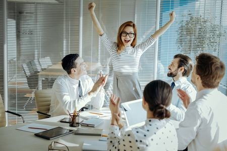 Exhilarating news. Upbeat young woman celebrating receiving good news during the meeting with her colleagues, raising her hands in triumph Stockfoto