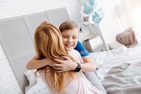 I love you. Happy cute delighted boy closing his eyes and smiling while hugging his mother 스톡 콘텐츠