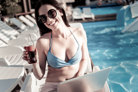 Waiting for you to join me. Cheerful young woman looking into the camera with a broad smile on her face while working on a laptop and holding a glass bottle of sparkling water outdoors.