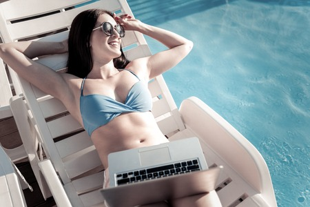 Vacation is calling. Radiant millennial girl wearing sunglasses looking into vacancy with a cheerful smile on her face while sunbathing with a laptop on her legs.