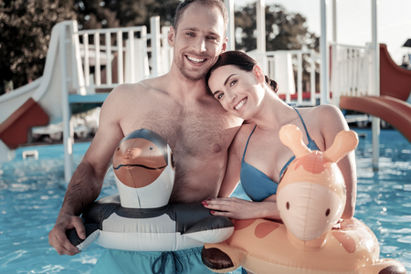 Back to childhood. Waist up shot of a joyful couple standing in a swimming pool and smiling cheerfully into the camera while both wearing colorful rubber rings.