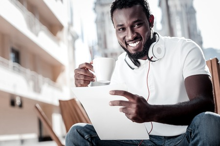 Positivity is the key to success. Low angle shot of a radiant African American entrepreneur grinning broadly into the camera while holding a contract and drinking coffee outdoors.