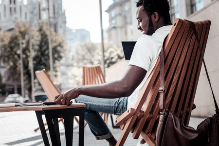 Young and successful. Positive minded self employed guy smiling while relaxing on a wooden chair with a touchpad in his hands and reading a message on his smartphone. Stock Photo