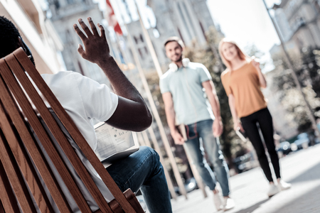 Hey there. Selective focus on a turned back African American man waving to his mates while meeting them in a local cafe.
