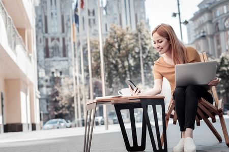Positivity is the key to success. Low angle shot of a happy millennial girl in casual reading a message with a cheerful smile on her face while working on a laptop outdoors. Stock Photo