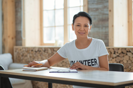 Attentive work. Positive pleasant female volunteer sitting at table while smiling and staring at camera