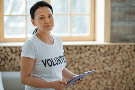 Volunteering abroad. Determined ambitious female volunteer holding clipboard while gazing at camera and posing on blurred background