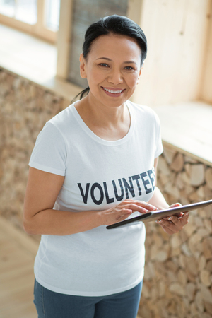 Gadget for volunteering. Top view of merry gay female volunteer standing on blurred background and using tablet while looking at camera Stock Photo