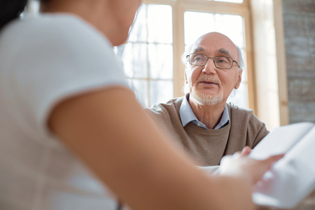 Daily routine. Smart thoughtful senior man talking while wearing glasses and looking at woman Stock Photo