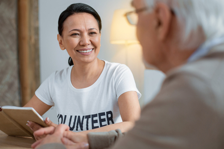 Wise thought. Jolly joyful volunteer grinning while holding notebook and staring at senior man Stock Photo