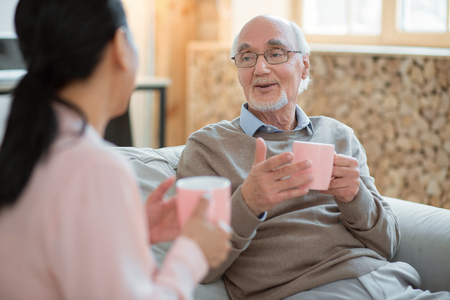 Funny conversation. Cheerful merry senior man chatting with caregiver while enjoying tea and laughing