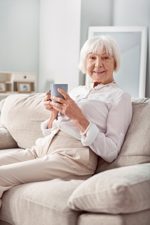 Pleasant morning. Pleasant senior woman sitting on the couch and posing for the camera while holding a cup of tea