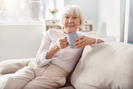 Delicious drink. Cheerful elderly woman sitting on the sofa in her living room and holding a cup of coffee while smiling at the camera Zdjęcie Seryjne