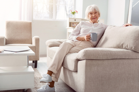 Relaxing pastime. Petite senior woman sitting on the couch, leaning comfortably against the backrest, and posing for the camera while holding a cup of coffee