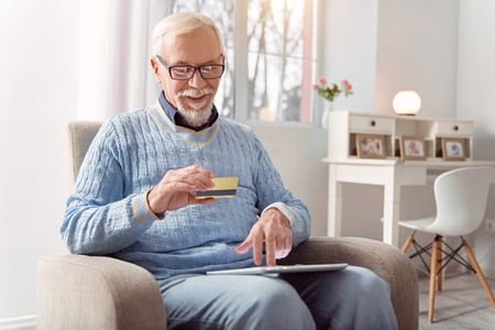 Convenient shopping. Charming elderly man sitting in the armchair and using his golden bank card while paying for his online purchases
