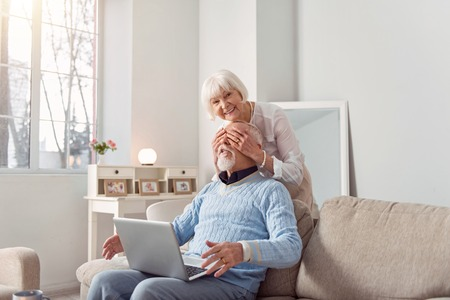 Pleasant surprise. Charming upbeat senior woman surprising her husband by covering his eyes from behind while he working on the laptop