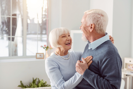 Loving couple. Joyful elderly husband and wife dancing in the living room while smiling at each other widely Stok Fotoğraf