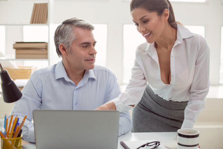 Pleasant communication. Joyful positive nice woman standing near her colleague and smiling to him while talking with him at work Stock Photo
