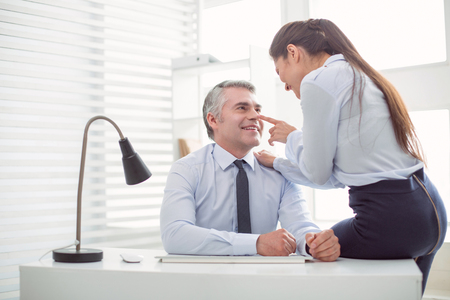 Relationships at work. Nice positive attractive woman looking at her boss and flirting with him while expecting a promotion