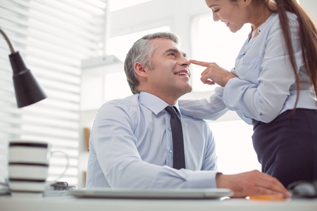 Flirting in the office. Happy nice handsome man looking at his colleague and smiling while flirting with her Stock Photo