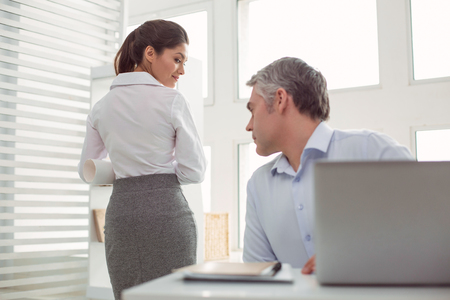 Inappropriate behaviour. Serious confident nice man sitting at the office table and showing his interest while being sexually attracted
