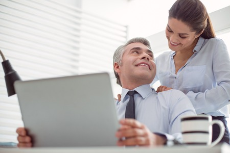 Personal relationships. Cheerful positive nice woman standing behind her boss and smiling while doing a massage for him Stock Photo
