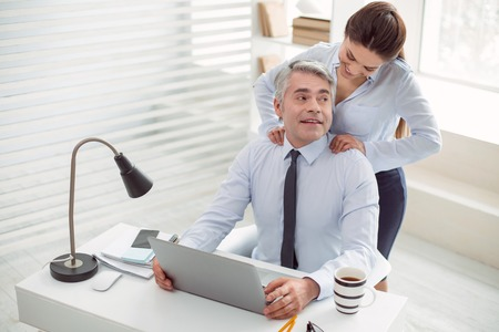 Pleasant relaxation. Nice positive happy man smiling and sitting at the table while enjoying the massage Stock Photo