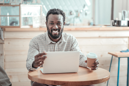 Professional freelancer. Joyful positive nice man sitting in front of the netbook and looking at you while working as a freelancer Stock Photo