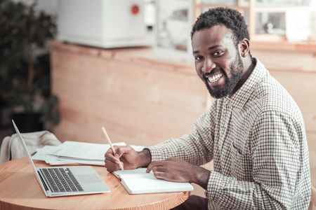 College student. Positive nice male student sitting at the table and looking at you while studying