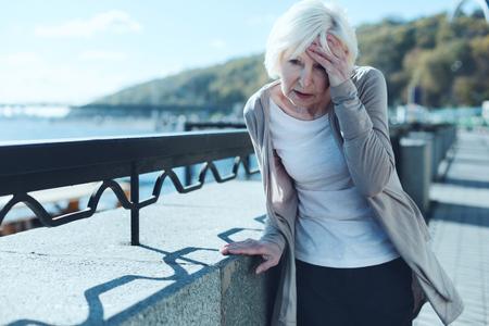 Necesito tomar mis pastillas. Señora mayor agotada apoyada en una barrera y tocando su frente mientras sufría de un terrible dolor de cabeza al aire libre.